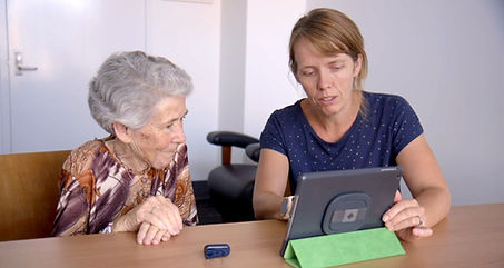 Older woman looking at tablet with physiotherapist