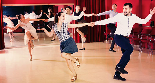 Happy dancing couples enjoying active swing in modern studio.jpg