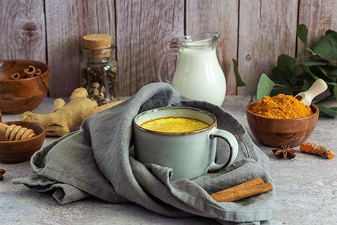 Golden turmeric milk with cinnamon, honey, and ginger. Ayurveda treatment. Alternative med