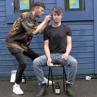 A guy from the public cuting the hair of a friend in a performative way, as the Happening was looking for things in between to happen