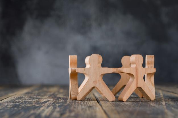 bonecos de madeira simulando pessoas de mãos dadas, fundo da imagem cinza, piso marron