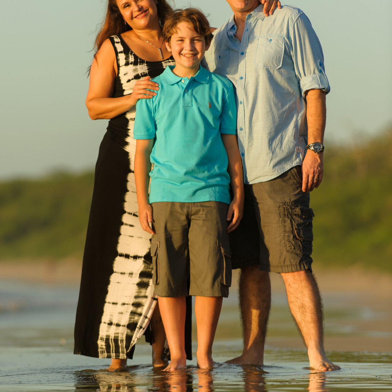 Mother, father and son dip toes into the sand at Hacienda Pinilla