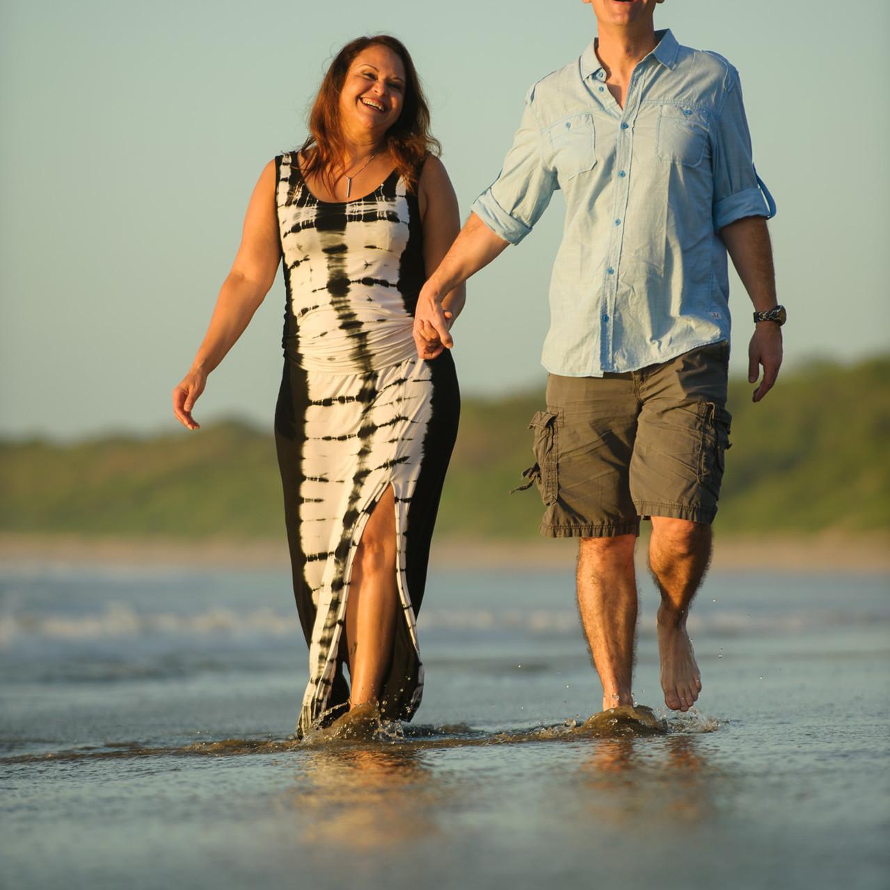 Husband and wife walk on the beach in Hacienda Pinilla