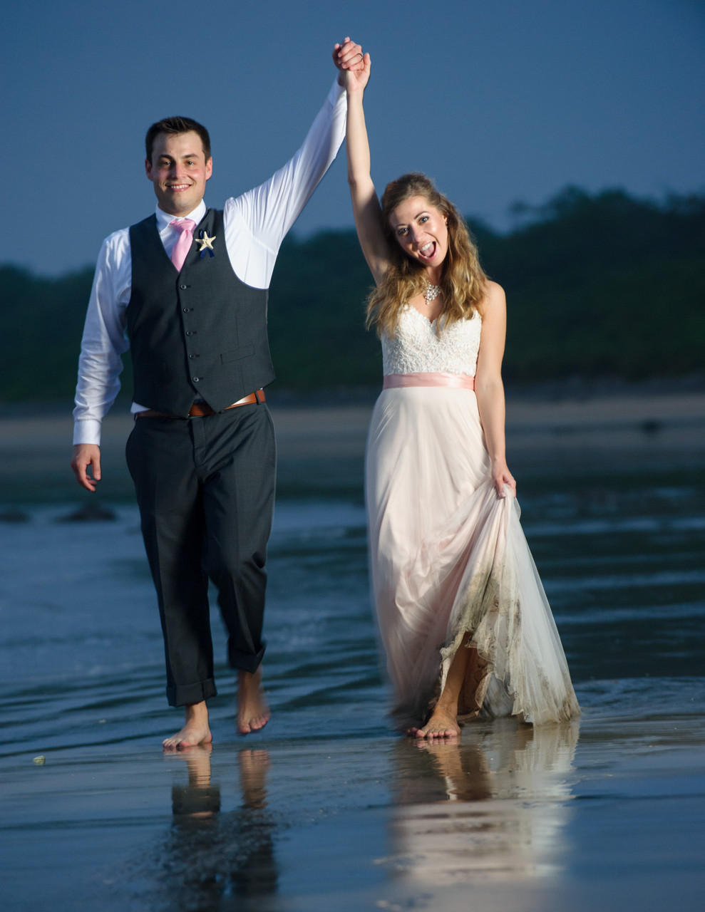 Bride and groom stroll on the beach in Hacienda Pinilla