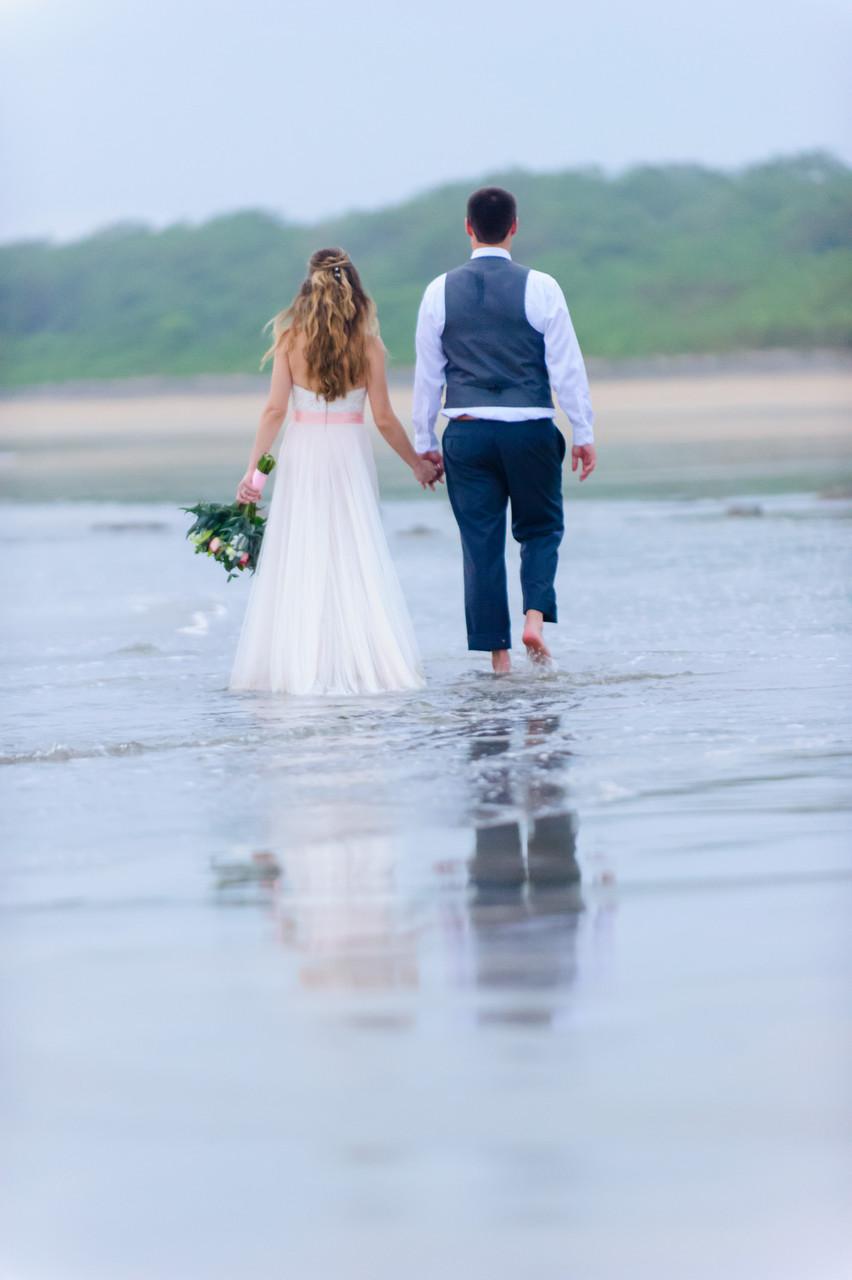 Bride and groom hand in hand on the beach in Hacienda Pinilla