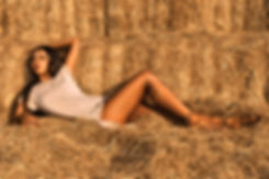 Fashion model in laying in hay.