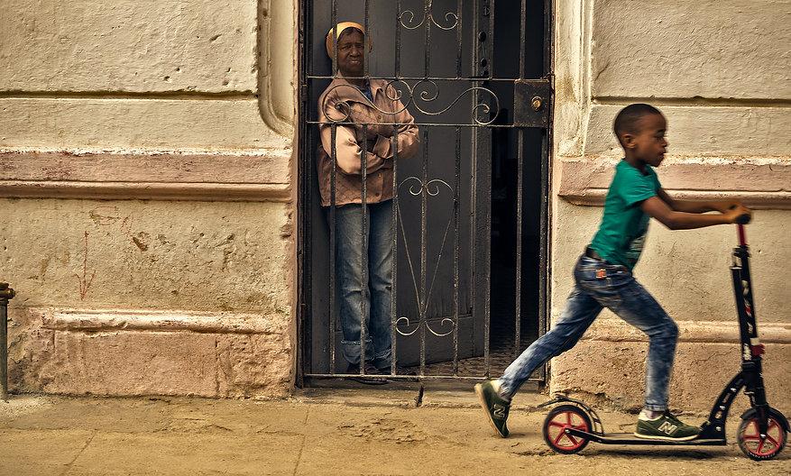 Woman standing behind gated door while child plays in street in Havana, Cuba.