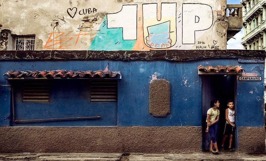 Photograph of two children standing beneath street art in Havana, Cuba.