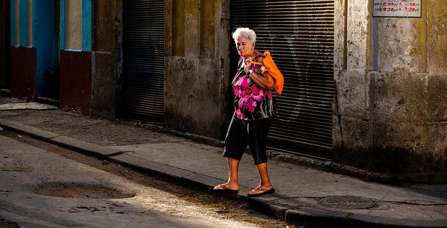 Portrait of old woman crossing street in Havana, Cuba.