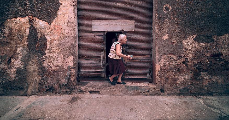 Portrait of old woman coming out of tiny door in Havana, Cuba.