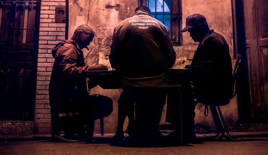 Photograph of domino players on the street of Havana Cuba at night.