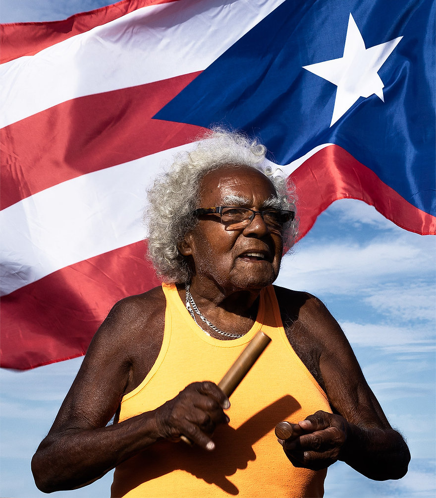Portrait photograph of an old Puerto Rican man dacing to salsa and playing the clave in front of the Puerto Rica flag.