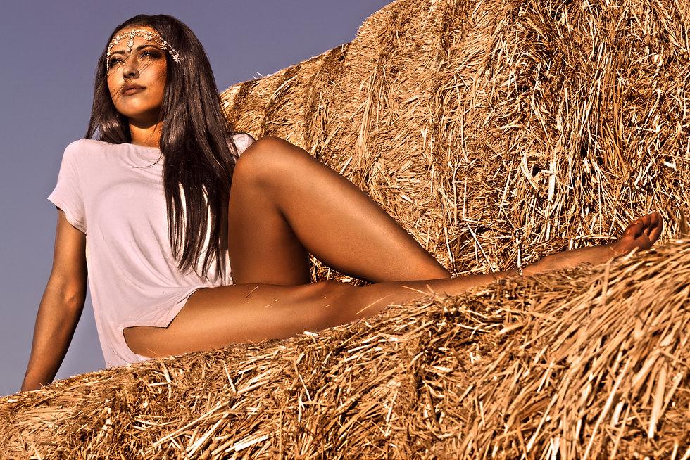 Fashion model posing on hay.