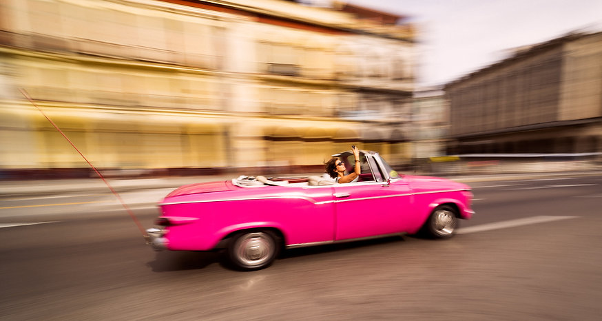 Potograph of tourist taking selfie in the back of a pink convertable driving through the streets of Havana, Cuba.