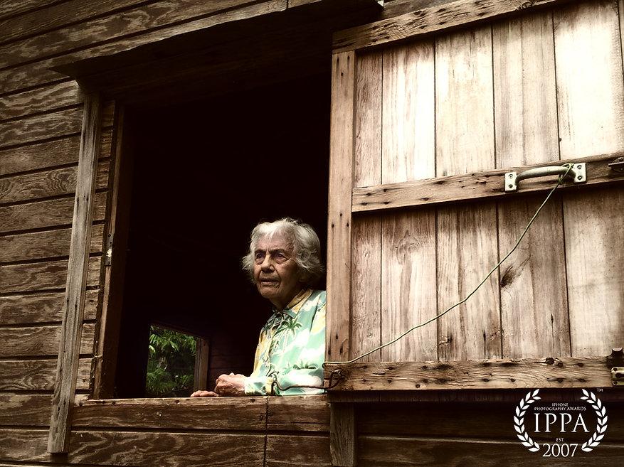 Award winning portrait of old woman in window.