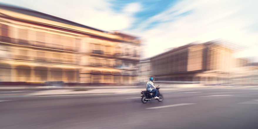 Photograph of motorcycle rider driving down the street of Havana, Cuba.