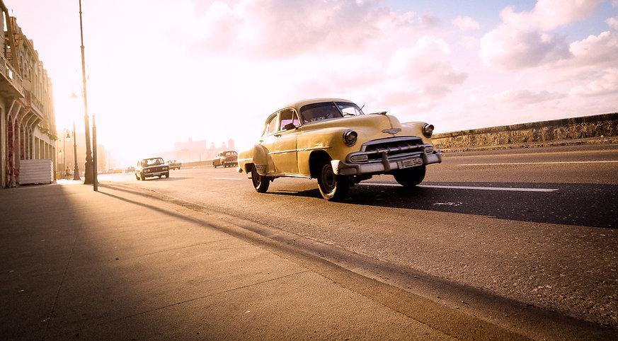 Photograph of calssic vintage Cuban car driving down the street of Havana, Cuba.