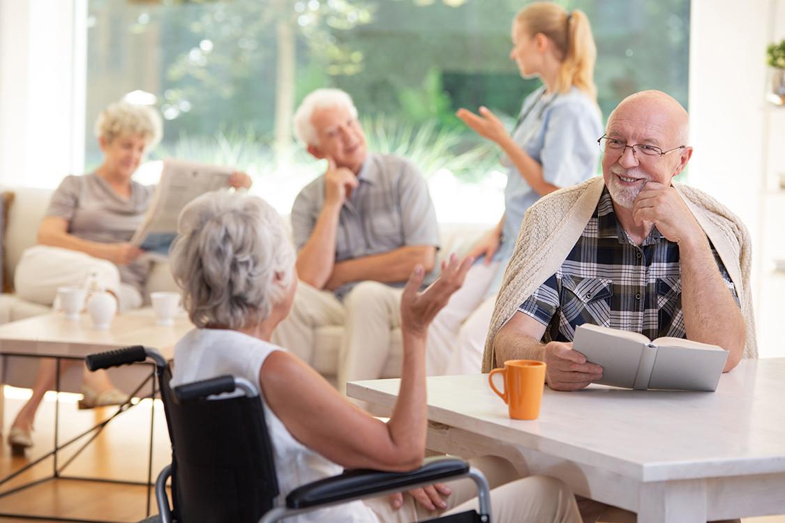 smiling-senior-man-with-book-talking-wit