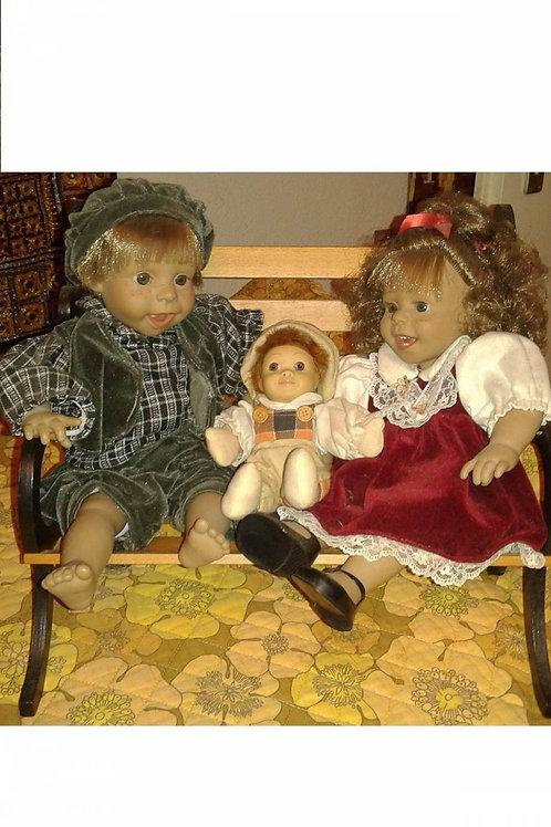 Drei sitzende Puppen