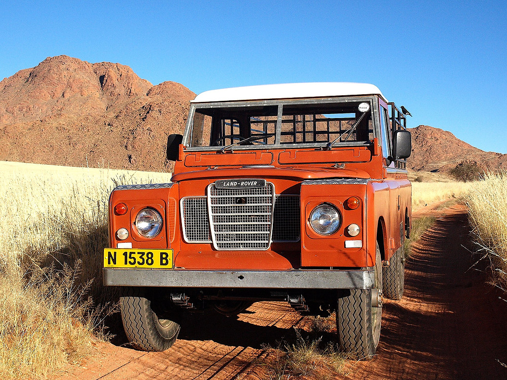 A red Land Rover Defender Series in the Namibian Desert with the Tiras Mountains in the back