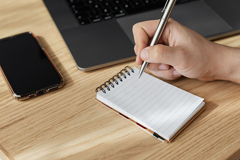 crop-person-writing-in-notebook-at-workp