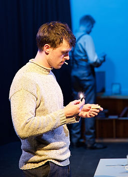 Harry Boaz as Franz in Motherland, lighting a cigarette with a match.
