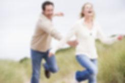 Couple running at beach smiling.jpg