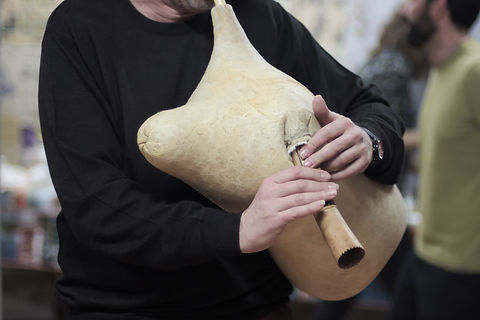 A musician is playing Greek bagpipe in a
