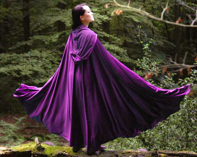 Women in the forest with a purple magic cloak