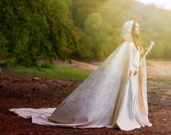 Woman in forest in white energy cloak