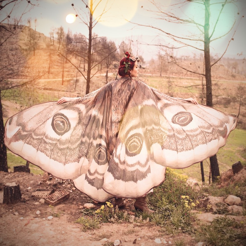 Woman in forest with butterfly cloak on.