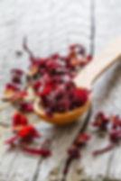 Dry hibiscus tea in wood spoon, rustic w
