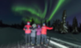 A group is photographed underneath the Aurora Borealis on Chase Dekker's private tour.