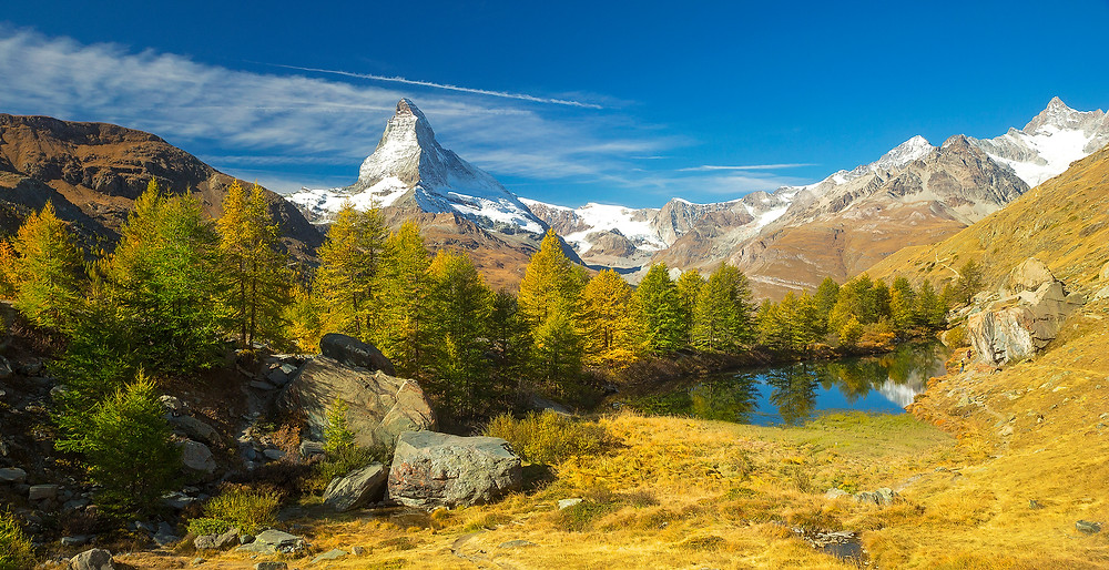 The Matterhorn towers above Grindjisee Lake and the fall foliage near Zermatt, Switzerland. Photographed by Chase Dekker.
