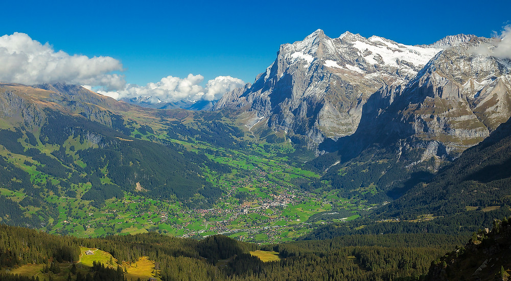 The village of Grindelwald lies far below Mannlichen with the Wetterhorn towering high above. Photographed by Chase Dekker.