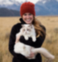 Hanna Glafke stands underneath the Grand Tetons with her cat. Hanna is the project manager for Chase Dekker Wild-Life Images.