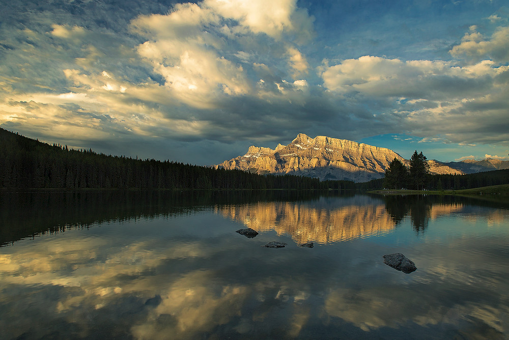 Mt. Rundle reflects off Two Jack Lake inside Banff National Park during sunrise. Photographed by Chase Dekker.
