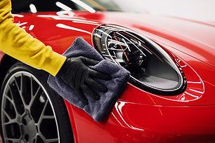 A man cleaning car with cloth, car detai