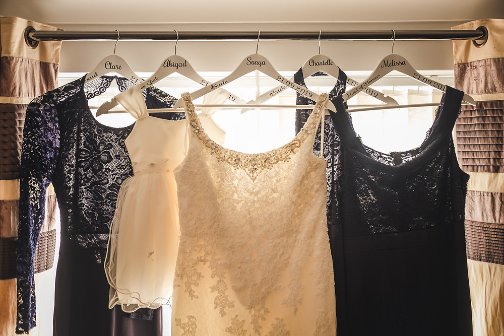 wedding dress and bridesmaid dresses hanging in the window