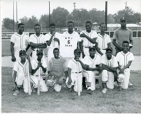 An all-black baseball team poses for a photo in black and white. Six players and the coach stand in a row, while seven players kneel on one knee in the front row. Most are smiling or have a small smirk.