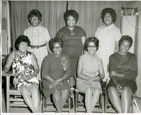 Seven women pose for a photo in black and white. Three stand women stand behind four others who are sitting in chairs.