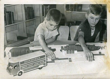 """Two young boys reach out to move blocks on a table as they build a library model. A toy truck with """"Bookmobile"""" on the side sits on the table next to them."""