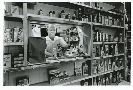 Richard Laws fills prescriptions in a window inside Laws Drug Store. Around the window are shelves of various products for sale. Image is in black and white.