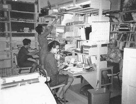 Women sit and stand in front of library shelving in a back workroom in a library. Two women in the foreground sit and type on typewriters. One woman in the middle of the image is reaching for something above her, while a fourth woman is also sitting and working on a typewriter.