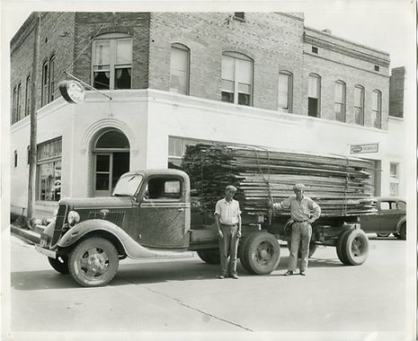 Two men stand in front of a 1930s model truck in front of a building in a black and white photo. The truck has a flat bed with logs on the back and one man leans on the load of the truck with his hand on his hip.