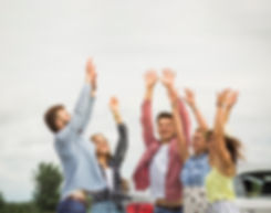 Happy-friends-raising-their-hands-at-out