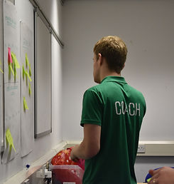 A man in a Coach tshirt putting post-it notes on a white board