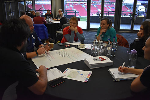Group of people around a table at a workshop with flipchart paper