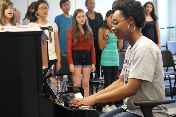 Teacher accompanies singing campers on the piano