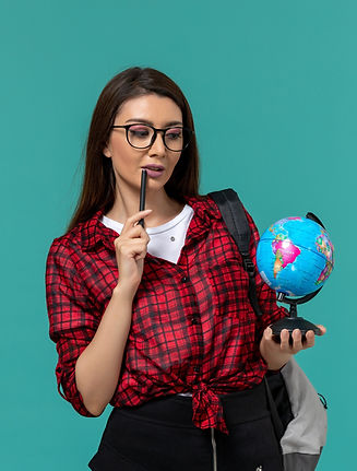 front-view-of-female-student-wearing-backpack-holding-little-globe-and-pen-on-light-blue-w